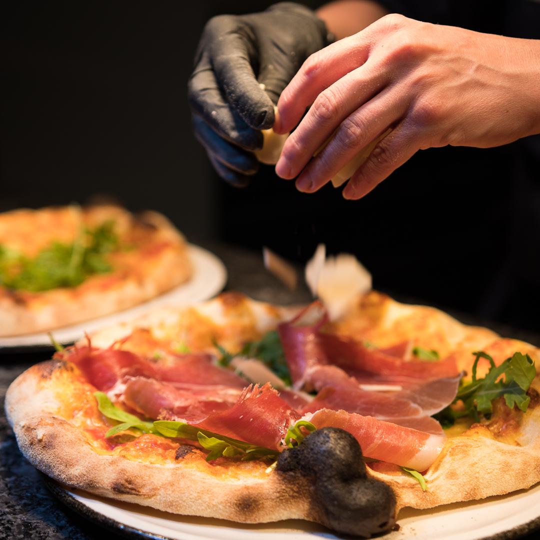 Pizza wird mit frischen Zutaten belegt